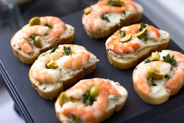 six pieces of bread, with cream cheese spread, topped with prawns, green olives and parsley