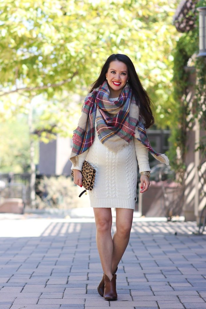 leopard print clutch bag, held by a smiling woman, dressed in a white knitted jumper, accessorized with a large plaid scarf, scarf outfits for warm fall days