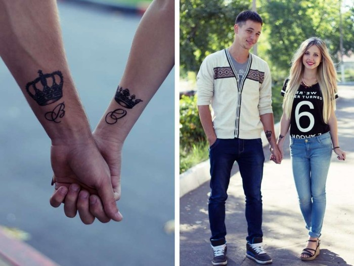 young couple holding hands, a close up reveals crowns, and letters tattooed near their wrists, matching tattoos for couples in love, king and queen