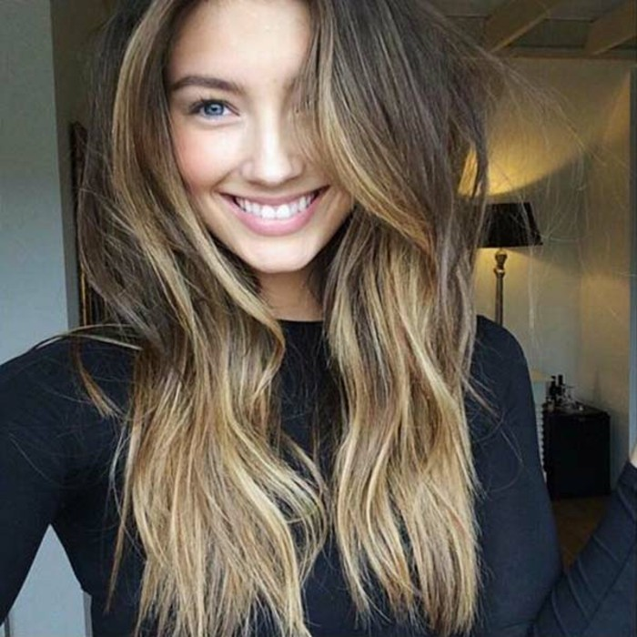 happy-looking young woman, with blonde balayage dark hair, wearing a black sweater