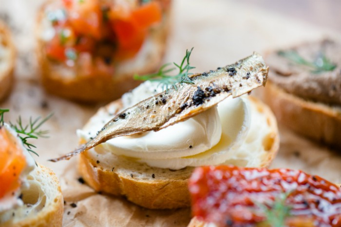 sardine dried and smoked, topping a piece of toast, smeared with creamy white spread, hor d oeuvres ideas for new year's eve