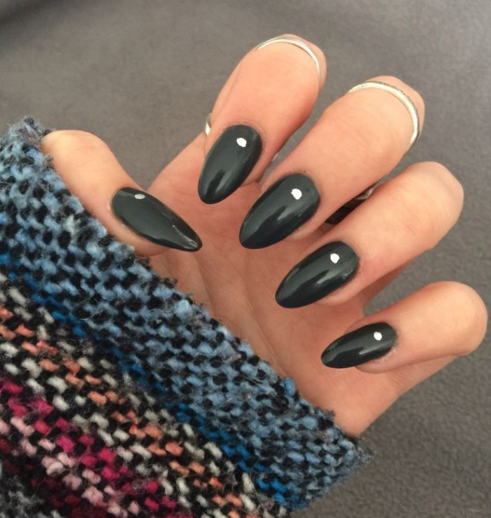multicolored knitted sleeve, worn by a pale hand, with folded fingers, and oval shaped nails, painted in black nail polish, and decorated with white dots