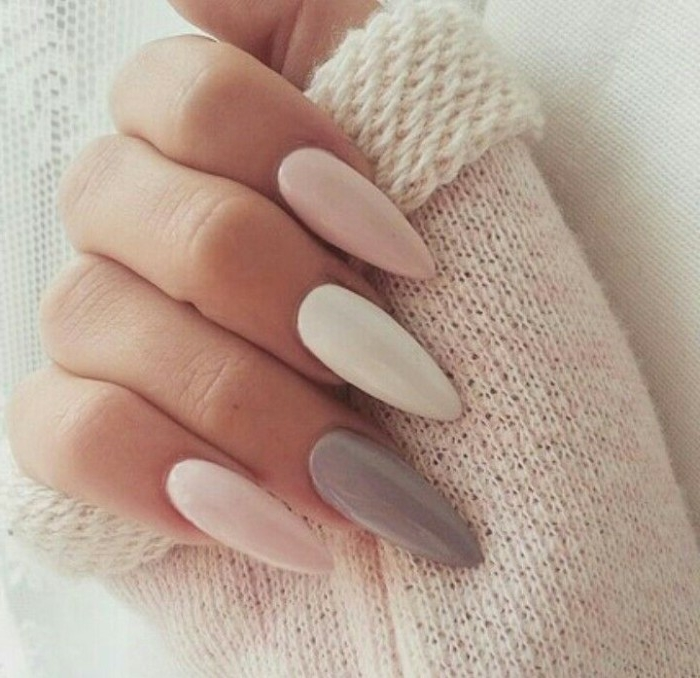 off-white fluffy sleeve, held by a hand, with a long and pointy manicure, white and pastel grey, and pink nude nails