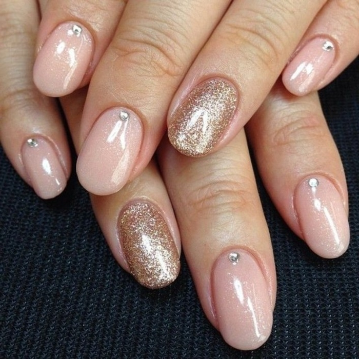 gem nail decals in silver, on an oval manicure, in pale pink, decorated with rose gold glitter, nude nails with glitter, on two hands, seen in close up