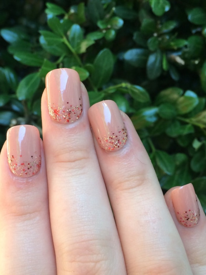 fine glitter in red and gold, decorating the base, of four square nails, painted in a nude nail polish, green tree in the background