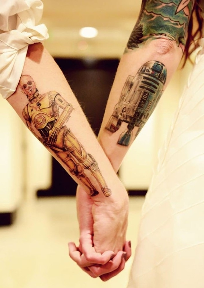 r2d2 and c3po, done in full color, on the lower part of two linked arms, matching tattoos for couples in love, and star wars fans
