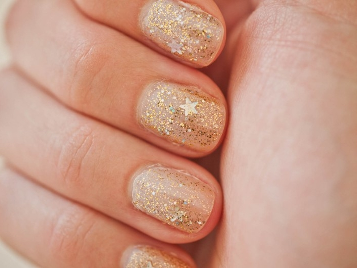 tiny stars and fine gold glitter, decorating four short nails, seen in extreme close up, nude nails with glitter