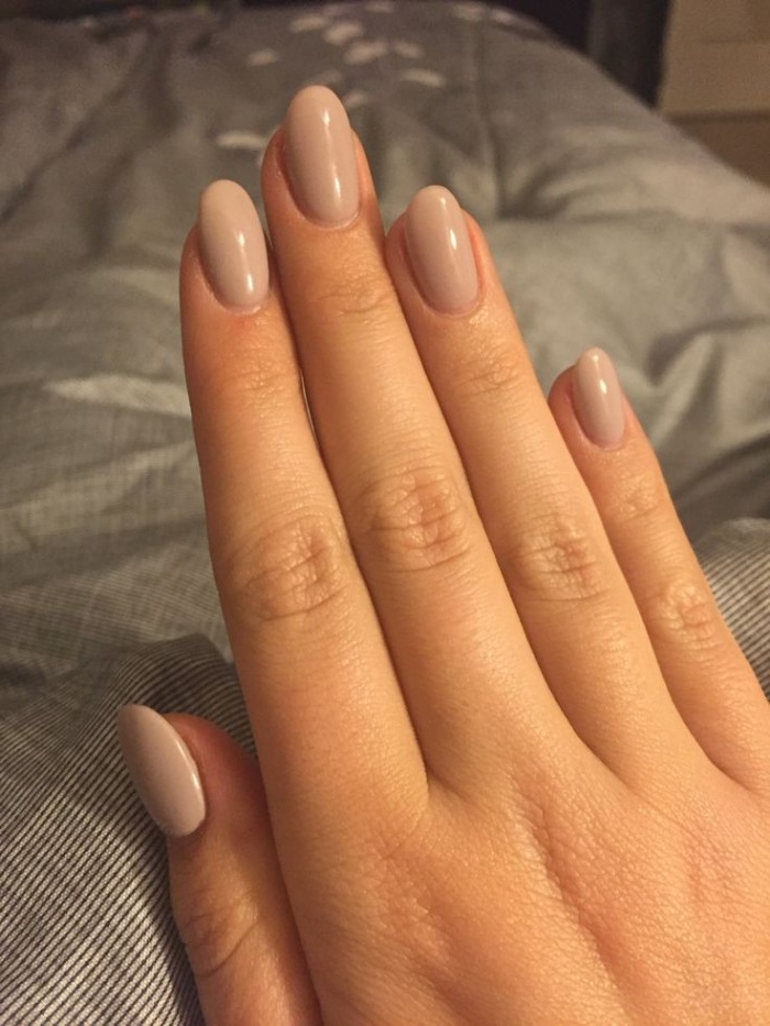five fingers of a stretched out hand, with an oval manicure, painted in a beige, nude nail polish