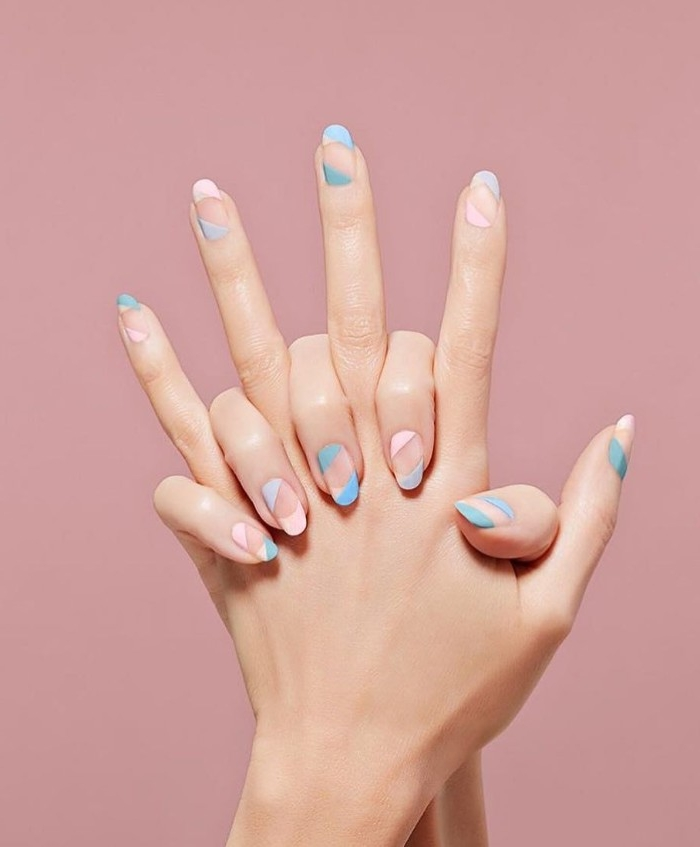 candy colored striped manicure, in pastel pink and turquoise, on the nude, oval shaped nails, of two hands