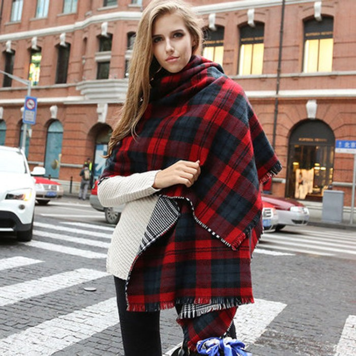 cape-like oversized reversable blanket scarf, in red and blue, and white and black, worn by a slim and tall, young blonde woman