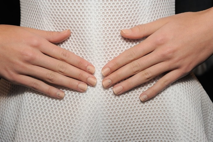 slim woman in a white dress, made from textured fabric, hands with plain, nude nail designs, placed on her stomach