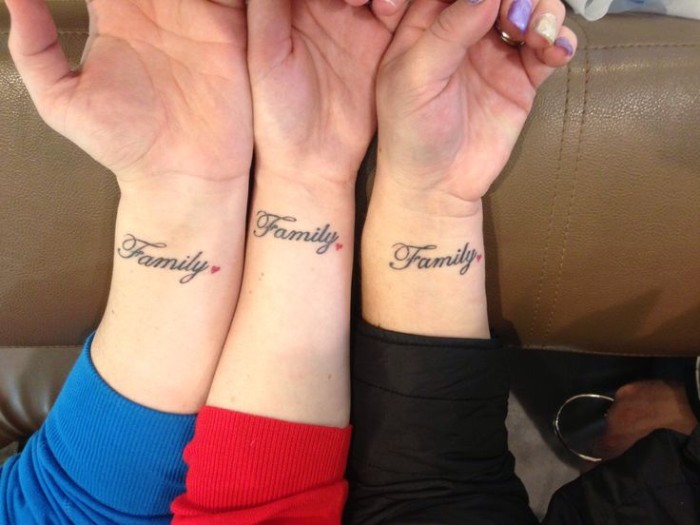 family tattooed in black ink, on the wrists of three arms, placed next to each other, matching sister tattoos, each is decorated with a small red heart