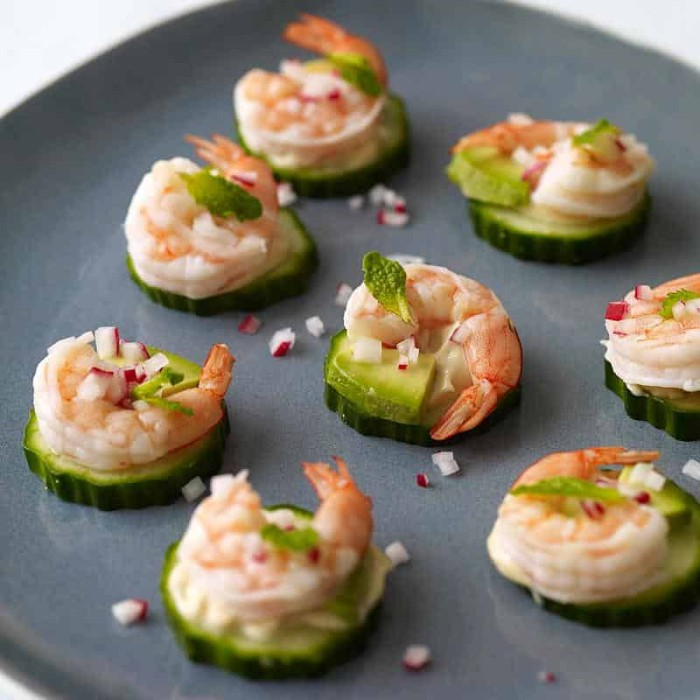 radish sprinkled on top of several appetizers, made with cucumber slices, topped with prawns