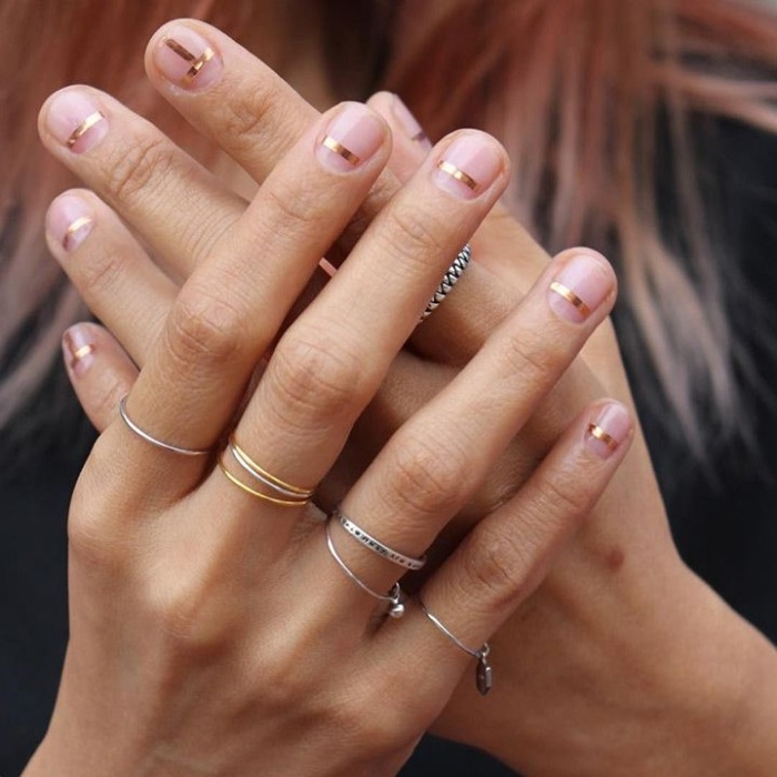 very short bare nails, each decorated with a thin, mettalic gold stripe, on two hands, with multiple thin rings