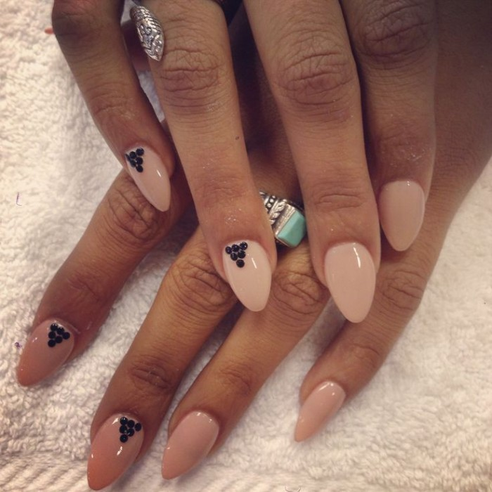 tan hands with nude nail polish, decorated with small black dots, pointy nails with almond shape