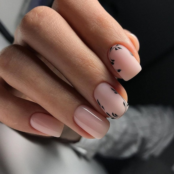 nude pink nail polish, on four nails, two plain and glossy, and two matte, and decorated with black, hand-drawn details