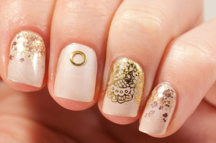 lace-like motifs in gold, gold glitter flakes, and a small ring-like sticker, on nude nail polish, decorating four square nails