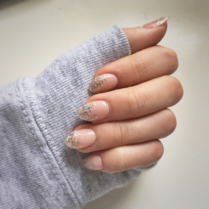 delicate short pointy nails, painted in nude pink nail polish, tips decorated with silver glitter