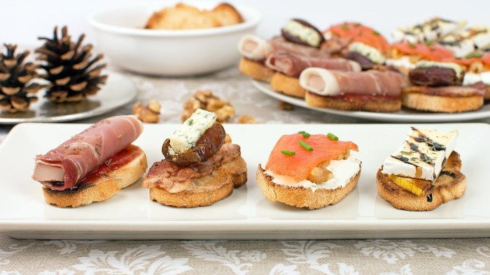 holiday horderves ideas, four slices of toasted bread, topped with cheese, smoked salmon and chives, prosciutto and other foods