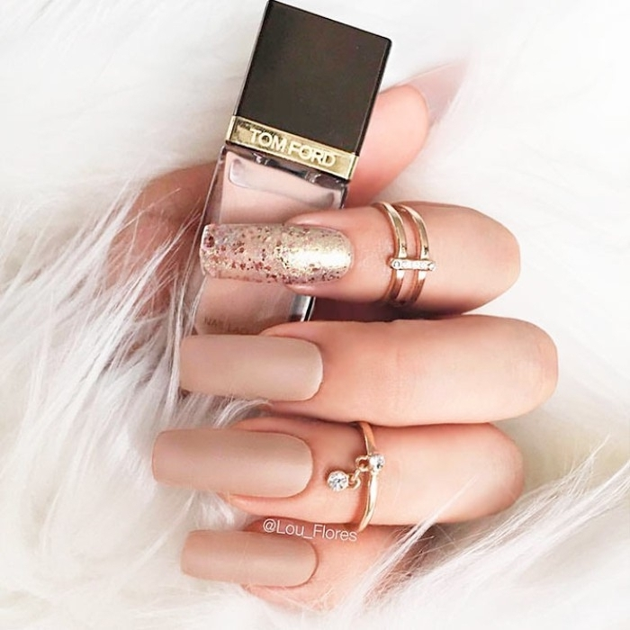 very long and square, nude matte nails, one decorated with metallic glitter, on a hand with two golden rings, holding a bottle of nail polish