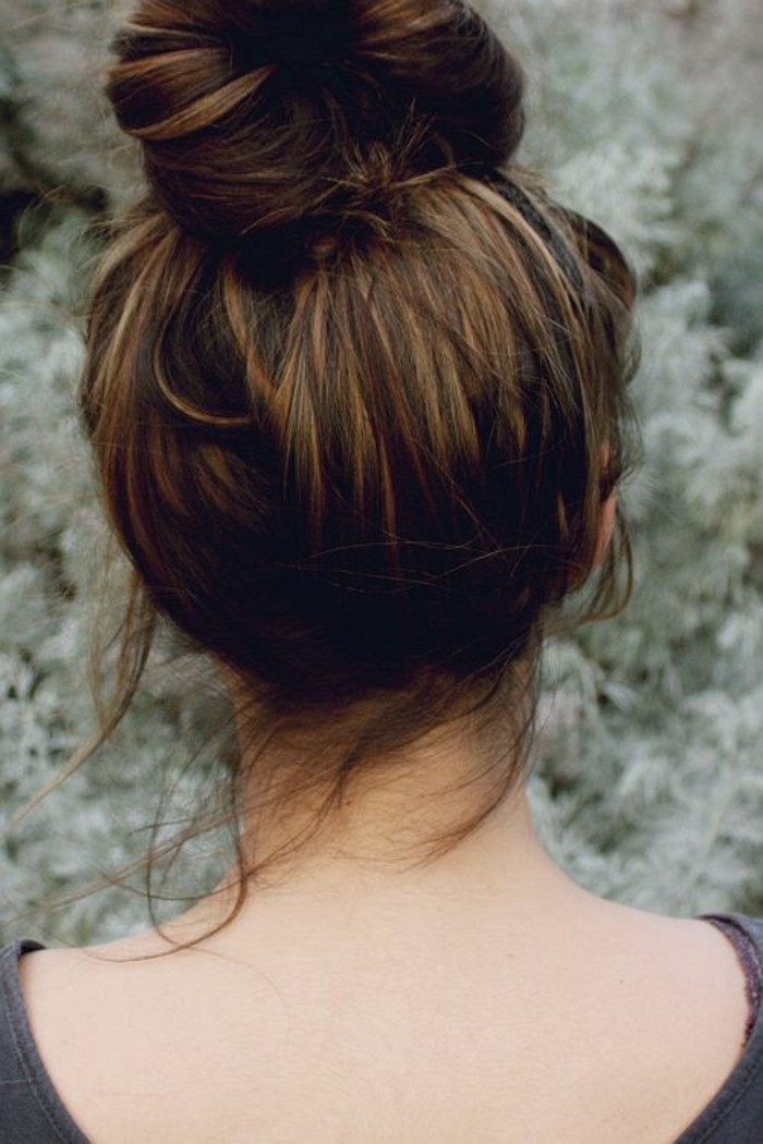 bun on top of the head of a brunette woman, with subtle dark blonde highlights, brown hair with blonde highlights, seen from the back