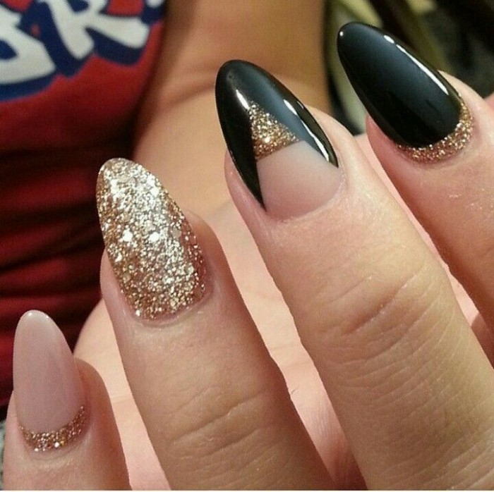 shimmering gold glitter, nude pink and smooth black nail polish, decorating four nails, attached to a pale hand