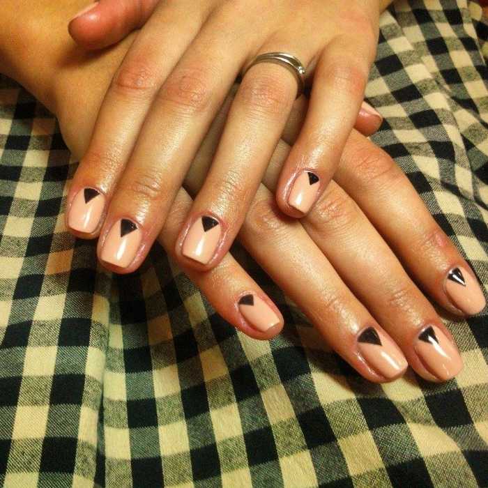 checkered fabric in white and blue, under two hands, with short nails, painted in nude pink, and decorated with small black triangles