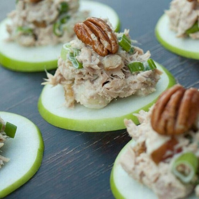 pecan nuts topping appetizers, consisting of apple slices, covered with tuna mayo, and green chopped onions