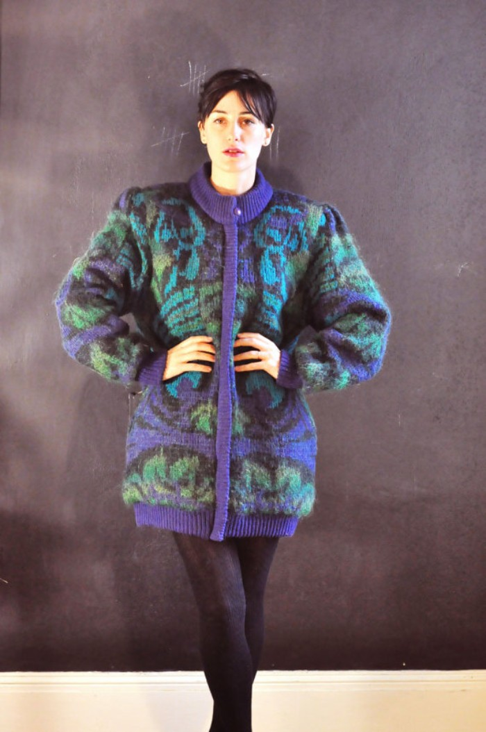 large patterned cardigan in black, turquoise and violet, worn over black opaque thights, 80s halloween costumes ideas, woman with black hair