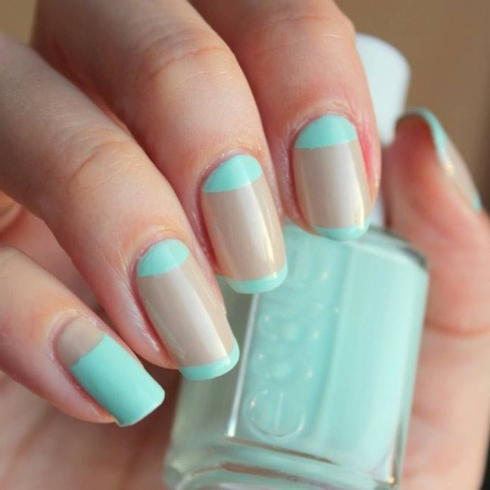 bottle of nail polish, held by a hand, with nude nails, decorated with turquoise stripes, oval shaped manicure