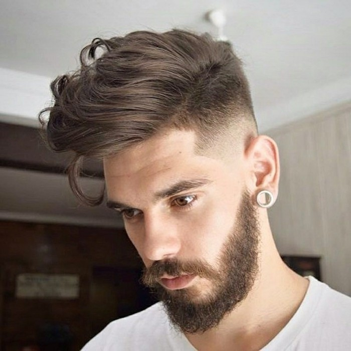 wavy chocolate brunette hair, styled to one side, with a connected undercut, modern haircuts for men, worn by a bearded young man, with a mustache and an earring