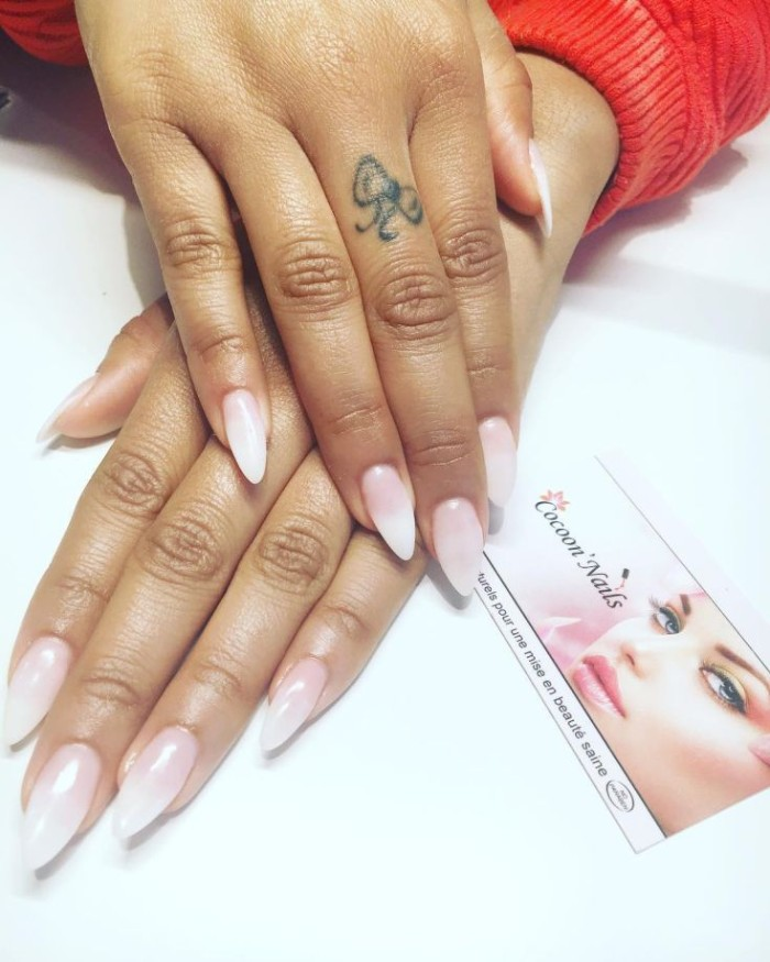 brown hands with pointy nails, painted in a pale, french manicure style, resting on a white surface