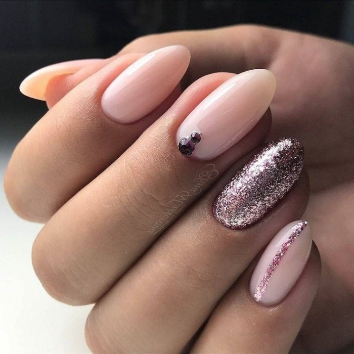 milky pink glossy nail polish, on an oval manicure, decorated with rose gold glitter, and purple gem nail decals, nude nails with glitter seen in close up