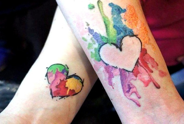 multicolored splashes with watercolor effect, and two heart shapes, matching tattoos for couples in love, done near the wrists of two arms