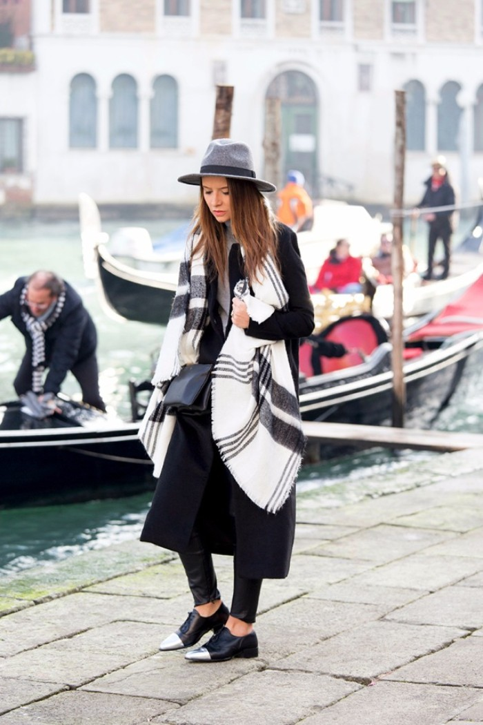 long black winter coat, worn by a brunette woman, in a pale grey hat, with a white oversized scarf, decorated with dark grey stripes