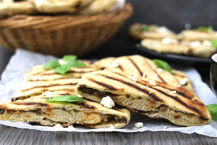 grilled flatbreads stuffed with vegetables, and peppered with white cheese, and fresh basil leaves, hor d oeuvres, placed on a white paper napkin