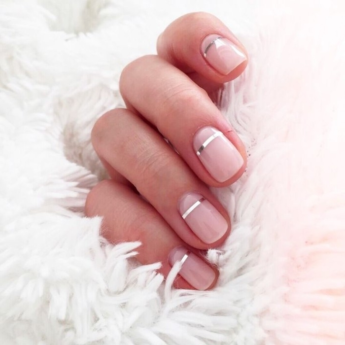 nude nails, each decorated with a thin, silver metallic stripe, on a hand, holding a white fluffy fabric