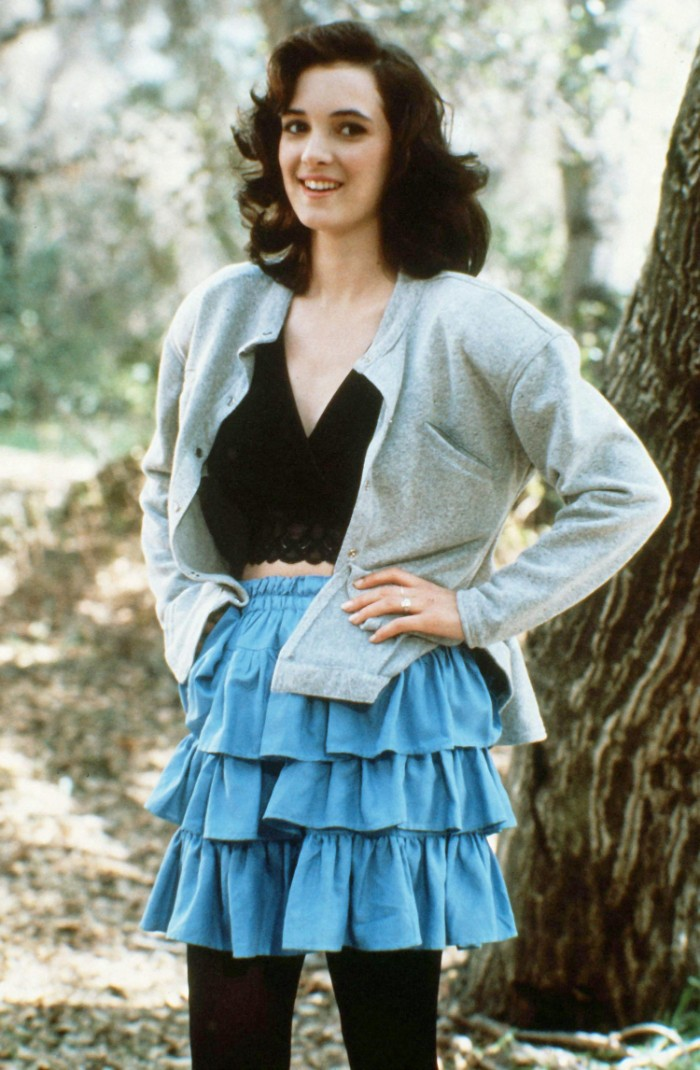 rara skirt in blue, worn with a black crop top, and a pale grey cardigan, by a young winnona ryder, 80's fashion pictures, smiling with hands on her hips, dress code nostalgia