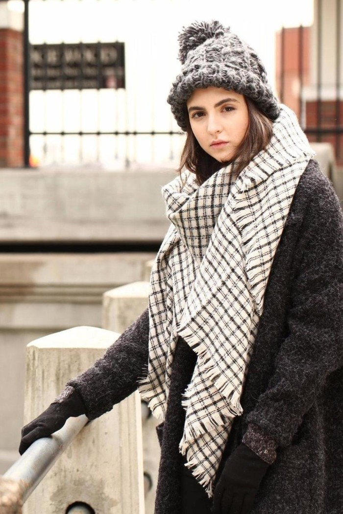 blanket shawl, in white and grey, worn by a young, brunette woman in a dark grey woolen coat, with a light grey, chunky knit beanie hat