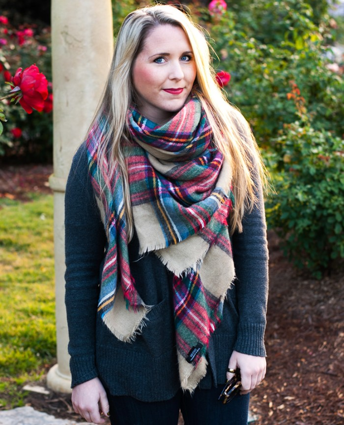 scarf outfits for fall, smiling blonde woman, with red lipstick, wearing a dark grey jumper, with an oversized plaid shawl, around her neck