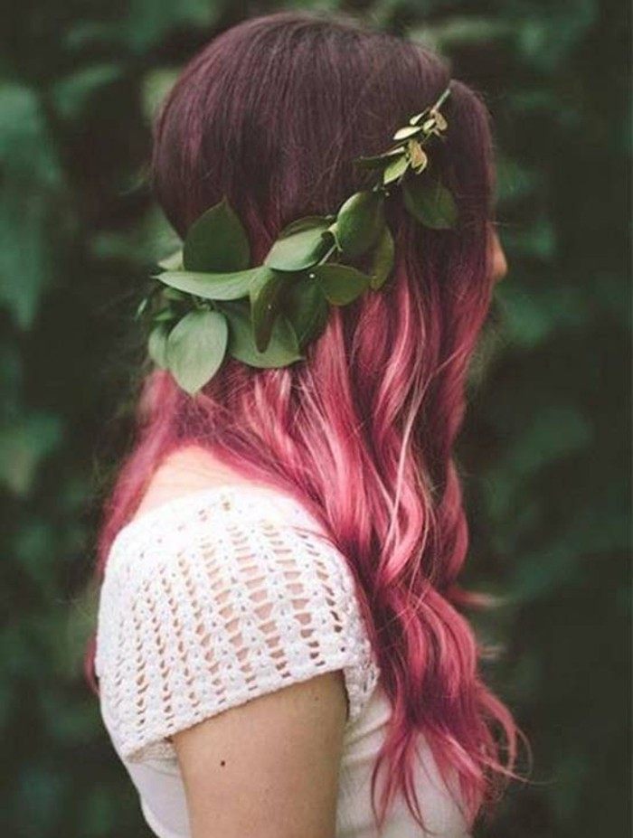 green leaf crown, decorating the head of a slim woman, with long pink hair, and dark roots