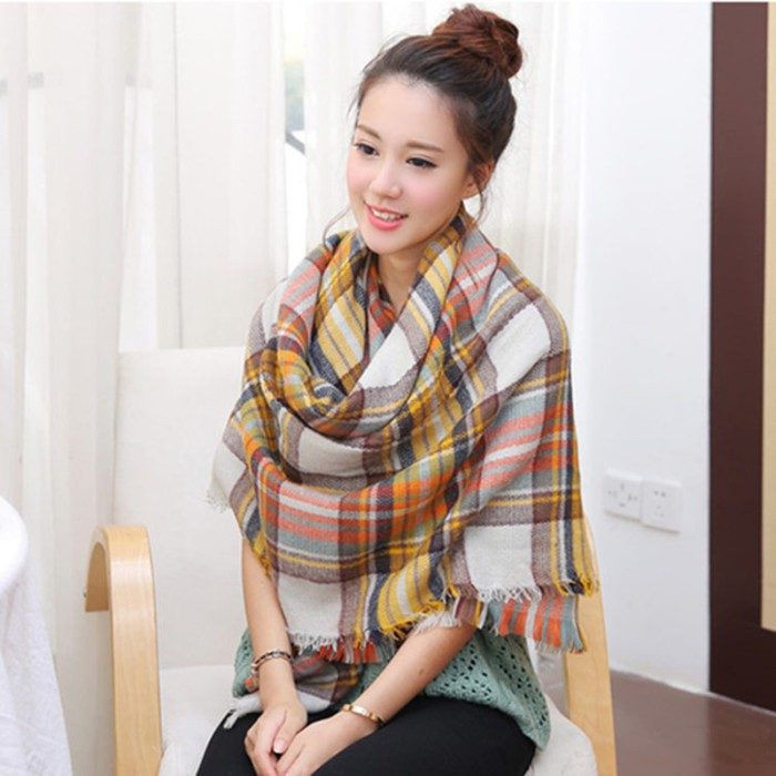 pale young east asian woman, with hair styled in a top knot, wearing a large scarf arounf her shoulders, in off-white, grey and yellow, and orange