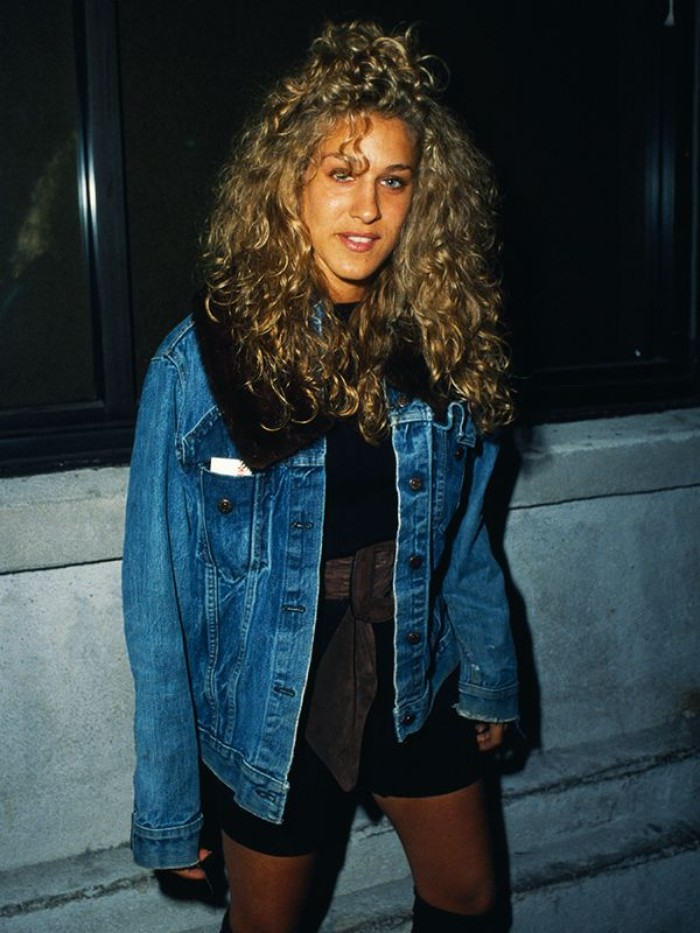 messy and curly long hair, on young sarah jessica parker, wearing a black, short jump suit, 80's fashion pictures, with a wide, dark grey belt, and an oversized denim jacket