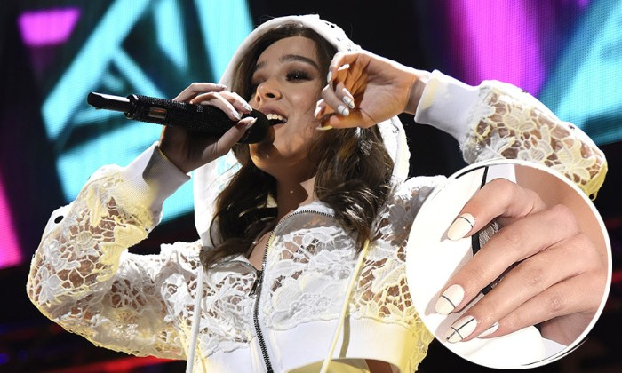 singer holding a microphone on stage, dressed in a white lace hoodie, close up of her hand reveals, white oval manicure, with thin black stripes