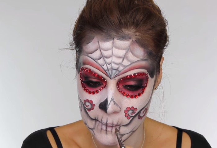 almost completed sugar skull makeup, halloween face paint, worn by a young woman, with brunette hair tied in a ponytail