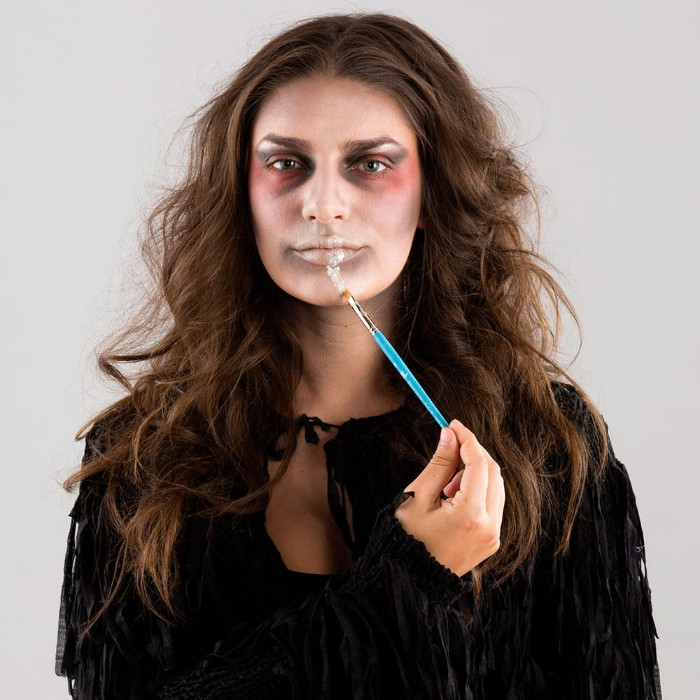 step by step photo tutorial, explaining how to create zombie face paint, young brunette woman, applying special effects makeup wax, on her lip, using a brush