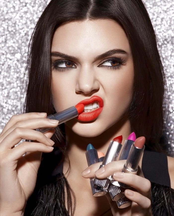 scowling young woman, with dark brunette hair, holiday makeup 2017, applying red lipstick with one hand, while holding five lipsticks, in different colors, with the other hand