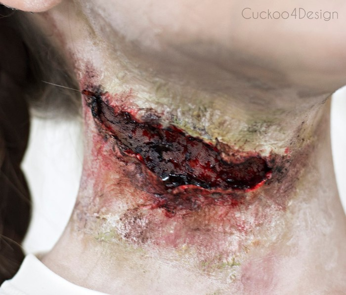 close up of a gory faux scar, facepaint ideas, created with special effects makeup wax, and fake blood, on the neck of a young girl