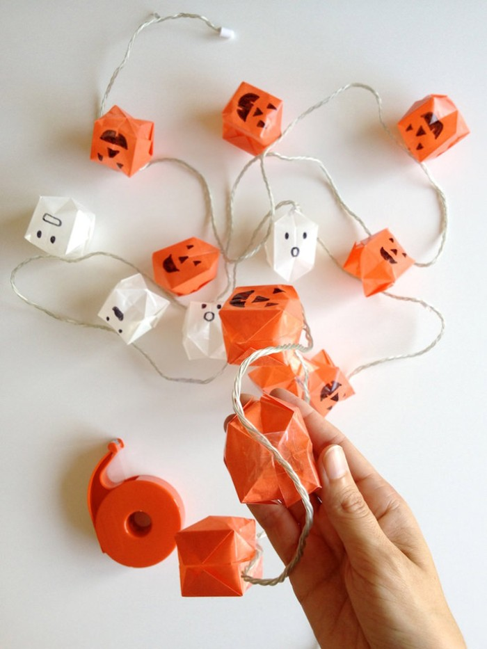 using sticky tape, to attach white and orange, paper origami shapes, with black hand-drawn jack-o-lantern faces, on a string of decorative lights