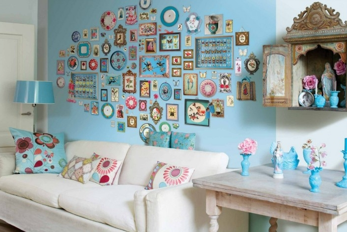 lots of framed images, in different shapes and sizes, on a baby blue wall, near a white couch, living room or dorm wall décor, antique elements and pop art
